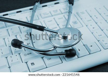 Stethoscope on white keyboard close up  - stock photo
