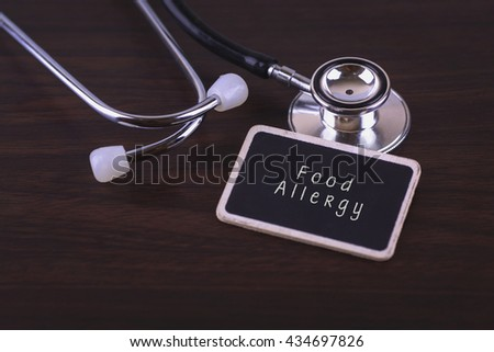 Stethoscope on wood background with Food Allergy words as medical concept - stock photo
