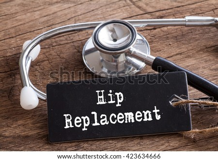 Stethoscope on wood with Hip Replacement words as medical concept - stock photo