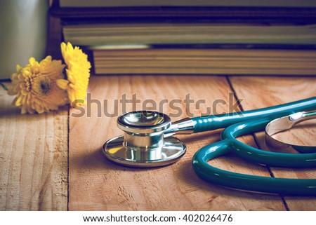 stethoscope on wooden table ,vintage tone.  - stock photo