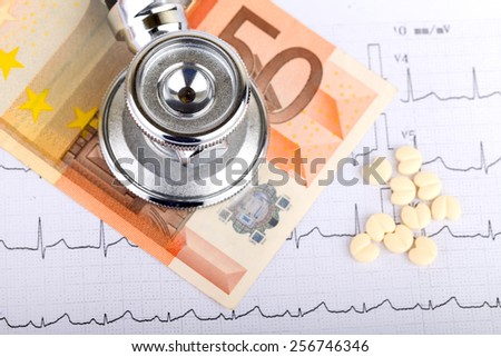 Stethoscope over electrocardiogram graph and 50 euro - stock photo
