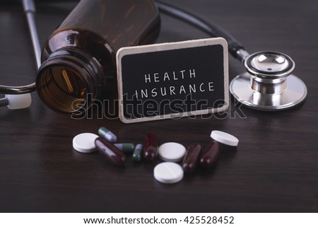 Stethoscope, pill bottle, Various pills, capsules and HEALTH INSURANCE on wooden background with copyspace area. - stock photo