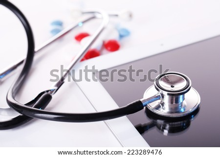 Stethoscope, pills, PC tablet on light background. Medicine concept - stock photo