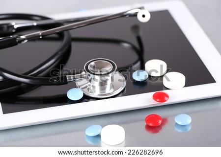 Stethoscope, pills, PC tablet on light background. medicine concept - stock photo