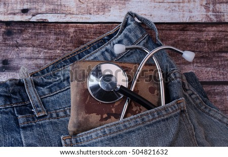 Stethoscope, purse with money looks out of a pocket of jeans.