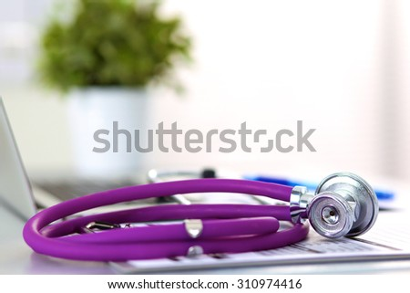 Stethoscope resting on a computer keyboard - concept for online medicine or IT support - stock photo