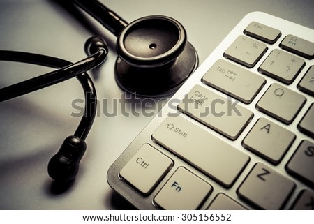 Stethoscope with computer keyboard - computer system maintenance and check concept - stock photo