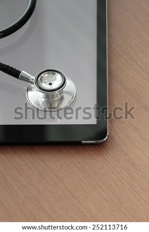 Stethoscope with digital tablet computer on wooden table and  background  - stock photo