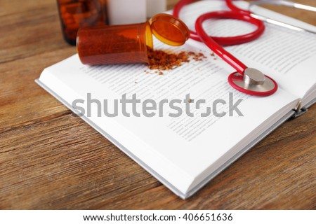 Stethoscope with dried herbs and open book on wooden table