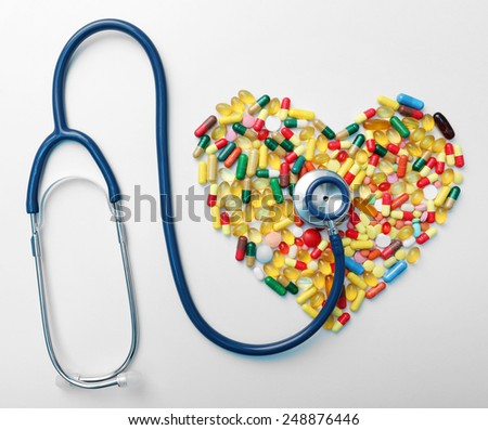 Stethoscope with heart from pills close-up - stock photo