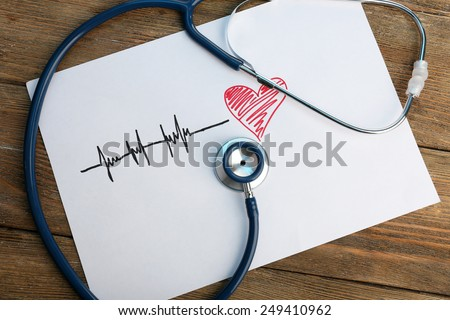Stethoscope with heart on wooden background - stock photo