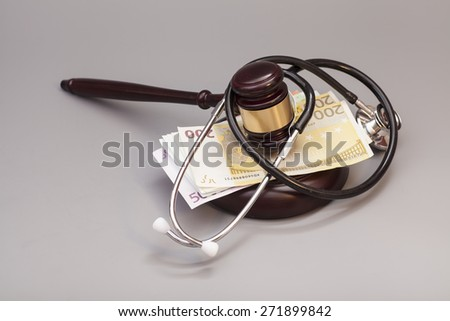 Stethoscope with judge gavel and euro banknotes on gray background - stock photo