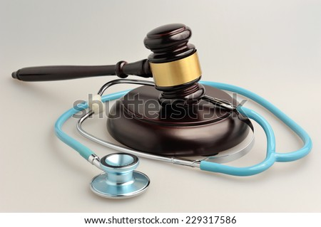 Stethoscope with judge gavel on gray background - stock photo