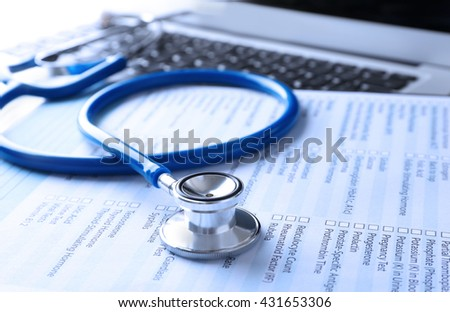 Stethoscope with medical form and laptop, close-up