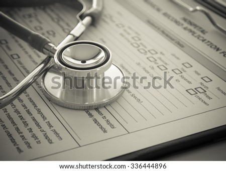 stethoscope with medical record application form on physicians desk - stock photo