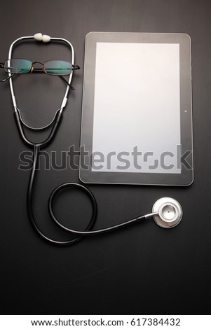 stethscope and a blank tablet on the blackboard