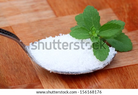 Stevia with spoonful of suger - stock photo