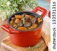 stew of beef with vegetables and prunes in a red cast iron pan closeup - stock photo