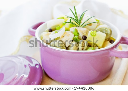 Stew of chicken, potatoes, beans and rosemary on the wood - stock photo