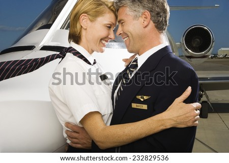 Stewardess and Pilot Hugging in Front of Private Jet - stock photo