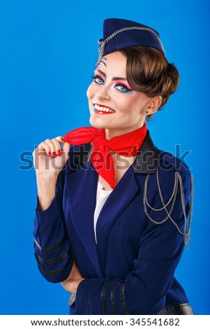 Stewardess with face art corrects neckerchief. Young attractive girl in a blue suit flight attendants. Airfreight. - stock photo