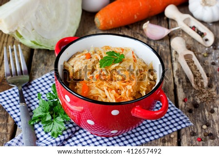 Stewed cabbage with meat, vegetables and spices on wooden table with ingredients selective focus - stock photo