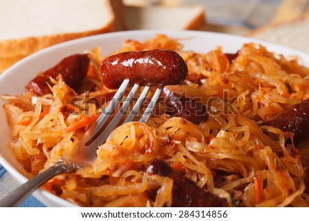 stewed cabbage with sausage macro in a white plate. Horizontal