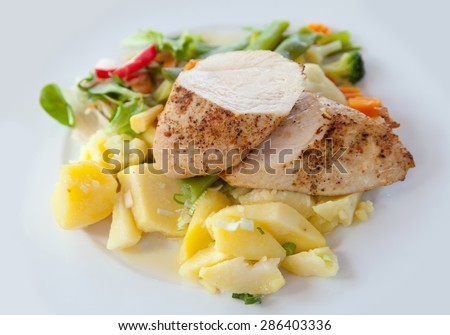 Stewed chiken with boiled potato on white plate - stock photo
