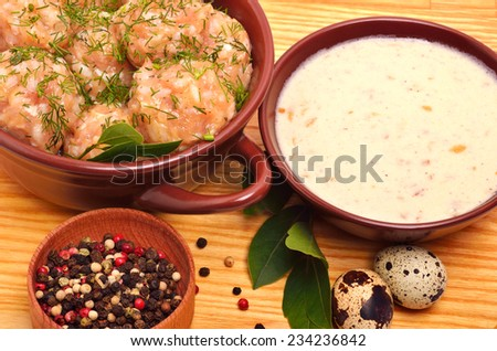 Stewed delicious meatballs in ceramic dish, quail egg and sour cream sauce in saucer on the wooden background isolated on white - stock photo