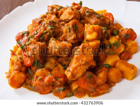 Stewed meat with vegetables in a plate on wooden table