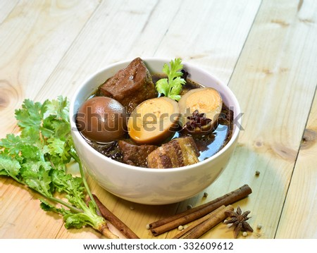 Stewed pork and egg in bowl on wood,selective focus