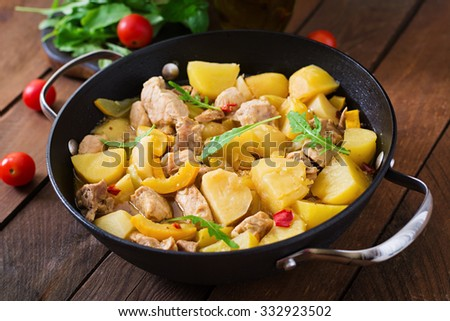 Stewed potatoes with meat and vegetables in a roasting tin on a wooden background
