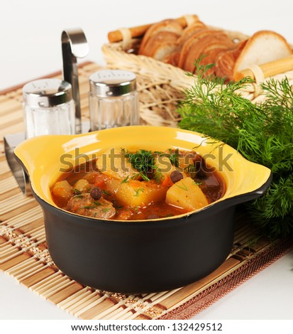 Stewed potatoes with meat in a ceramic pot. - stock photo