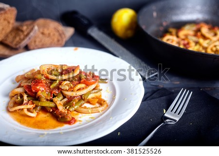 Stewed squid rings with tomato sauce and chilli in white plate. Dark wood background with bread on back