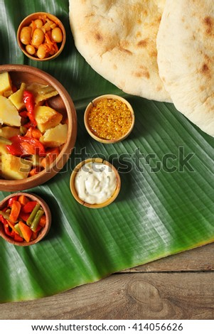 Stewed vegetables with spices and flat bread on banana leaf over wooden background