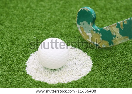 Stick and ball on a green grass - stock photo
