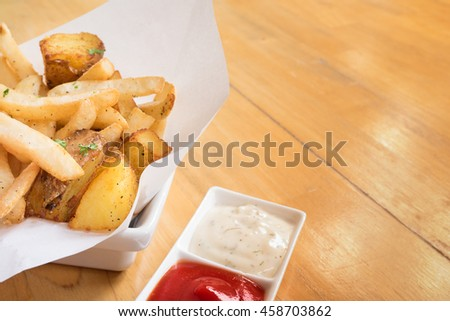 Stick and wedge French fries on white bowl with white paper sheet and a square cup of tomato sauce and mayonnaise - empty space for text - stock photo
