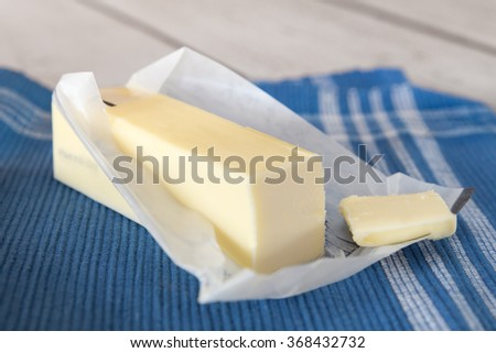 Stick of creamery butter in opened wrapper - stock photo