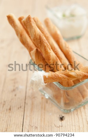 Sticks made of french dough served on party as a snack with cream dip with chive