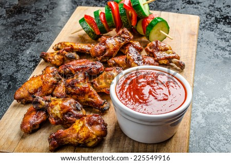 Sticky chicken with red hot dip and vegetarian skewers - stock photo