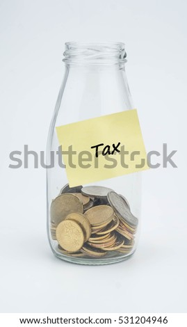 Sticky note on glass jar with word tax. Financial concept