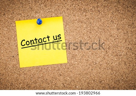 sticky note with word contact us on corkboard, business concept - stock photo