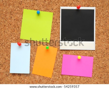 sticky notes and photo frame over brown cork background - stock photo