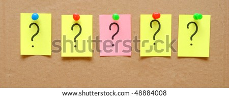 sticky notes with question marks over cardboard - stock photo