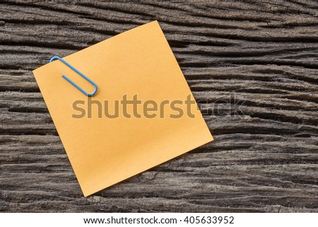 sticky paper note holding by clip on the old wooden background - stock photo