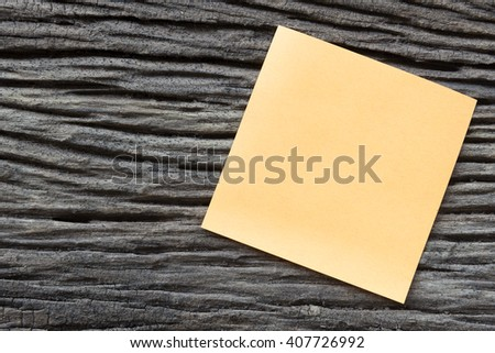 sticky paper note on the old wooden background - stock photo