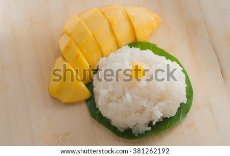Sticky rice mangoes with coconut milk ,banana leaf, On wood