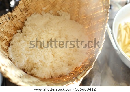 Sticky rice steam cooking in a bamboo basket. - stock photo