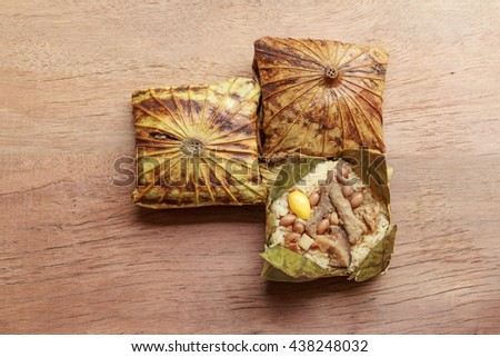 Sticky rice wrapped in lotus leaf or Zongzi is traditional Chinese food on wooden background. - stock photo