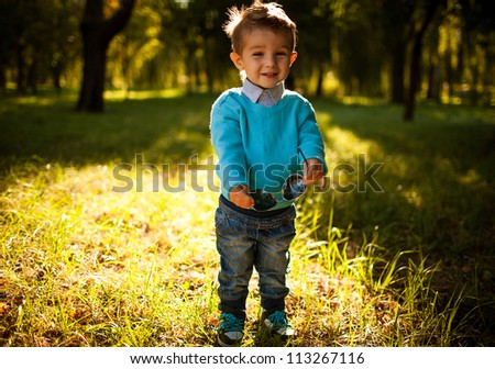 stilish baby boy having fun outside in the park,laughing